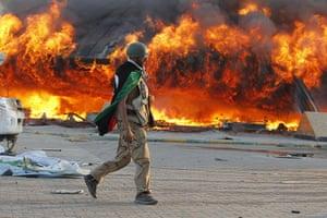 Gaddafi's compound falls: A Libyan rebel walks in the Bab al-Aziziya compound in Tripoli