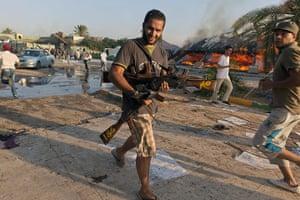 Gaddafi's compound falls: A rebel carries guns he's taken