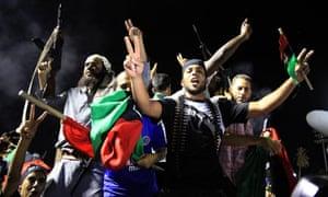 Rebel fighters in Libya celebrate the capture of Muammar Gaddafi's compound