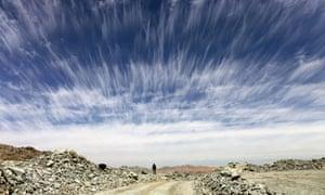 A man walks beneath an unusual cloud formation