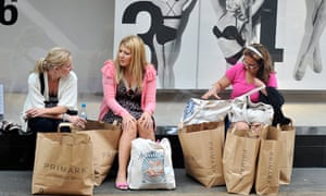 Woman sit with their shopping bags in central London
