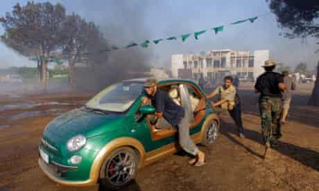 Rebels and car in Gaddafi compound
