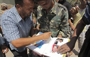 Raids in Tripoli: Rebel fighters look through an album including pictures of Condoleezza Rice