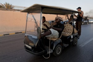 Raids in Tripoli: Fighters ride in a golf buggy taken from Gaddafi's headquarters
