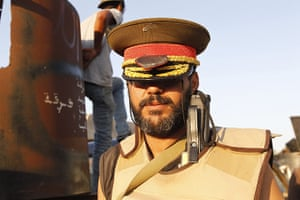 Raids in Tripoli: A Libyan rebel poses with a hat belonging to Muammar Gaddafi