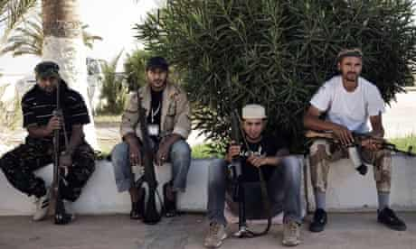 Libyan rebel fighters rest outside a mosque as they prepare to advance on Sirte