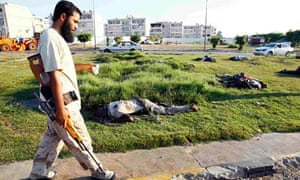A Libyan rebel walks past dead bodies in Tripoli. Evidence has emerged of executions on both sides