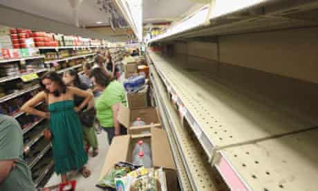 People wait in line to buy groceries next to empty shelves in a Manhattan grocery store