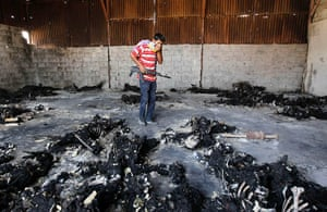 24 hours in pictures: A rebel fighter looks at the charred remains of burnt bodies, Tripoli