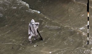 24 hours in pictures: A man stands on a water-logged street during heavy rains in Mumbai