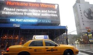 A taxi passes by a Hurricane Irene warning sign