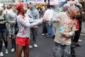 Notting Hill carnival: A reveler throws powder at the start of the Notting Hill Carnival
