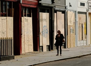 Notting Hill carnival: A woman passes boarded up shops ahead of the annual Notting Hill Carnival