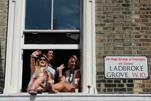 Notting Hill carnival: Women wave from a window as they watch the parade, Notting Hill Carnival