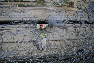 24 hours: Mach, Pakistan: A rescue worker is seen through the bullet-riddled window