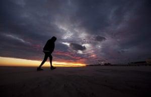 24 hours: Long Beach, New York, USA: A woman walks off the Long Beach Park beach