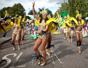 Notting Hill - Day 2: A reveller dances as they parade through the streets