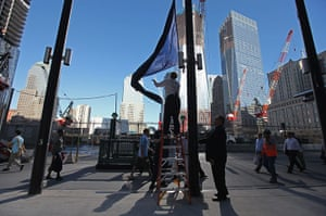 After Hurricane Irene: Millenium Hilton hotel staff raise New York flag in front of the hotel