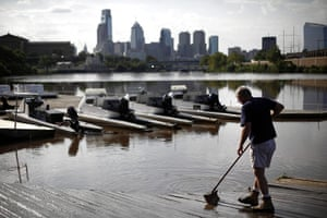 After Hurricane Irene: A man sweeps silt left behind from the floodwaters of the Schuylkill River