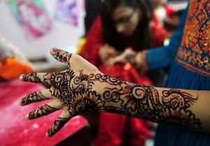 Eid al-Fitr: Karachi, Pakistan: A beautician applies traditional henna designs