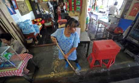 thai floods a woman clears floodwater