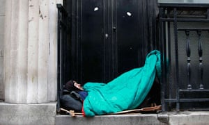A homeless man sleeps in a doorway in central London