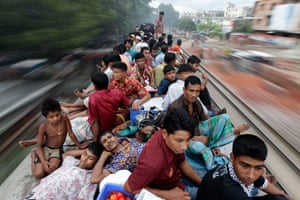 Eid Festival: Passengers sit on top of an overcrowded train as it heads for Jamalpur