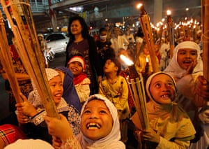 Eid Festival: Children march through a street carrying torches to mark the end of Ramadan