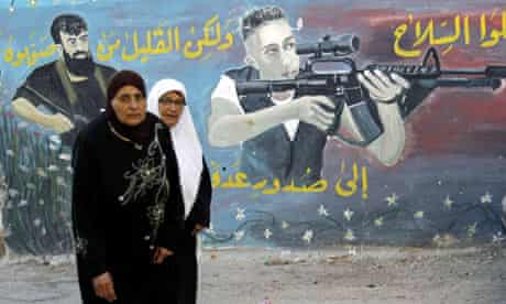 Palestinian women walk next to a mural of militants in the West Bank town of Jenin