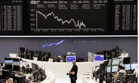 A photographer waits to take a picture in front of the DAX board at the Frankfurt stock exchange
