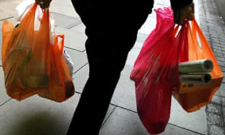 A woman carries her shopping with free supermarket shopping bags in London