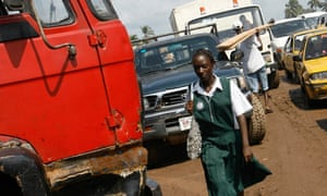 liberian schoolgirl walks through traffic jam