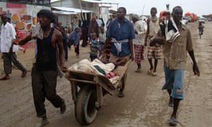 Refugees push a man injured in the clashes in Mogadishu