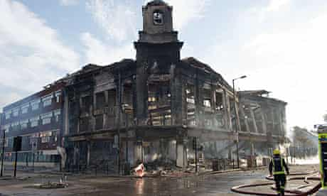 In Tottenham, firefighters survey the burnt out shell of a carpet showroom on Tottenham High Road