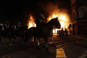 Tottenham riots: Mounted police ride in front of a burning building