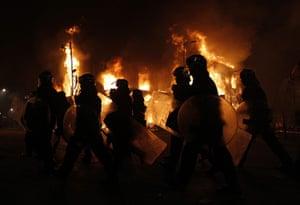 Tottenham riots: Police officers wearing riot gear walk past a burning building in Tottenham