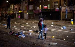 Tottenham riots: A woman and her child walk through the debris