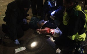 Tottenham riots: Riot police treat a man for his injuries before arresting him in Tottenham