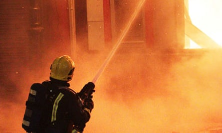 A firefighter attempts to control flames as a building burns during the Tottenham riots