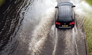 A car drives along a flooded road after heavy rain in north-east England