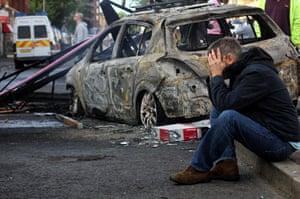 Tottenham riots: A local resident next to a burnt car