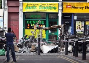 Tottenham riots: A man photographs a burnt out bus on Tottenham High Road
