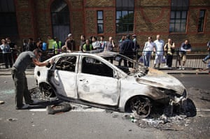 Tottenham riots: A man photographs a burnt out police car