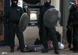 London riots: Police officers detain a man in Enfield, north London
