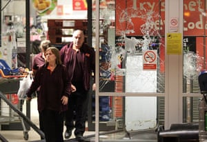 London riots: Staff leave a damaged Sainsbury's sstore in Enfield