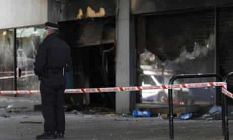 A policeman stands outside damaged shops in Brixton after a second night of rioting in London