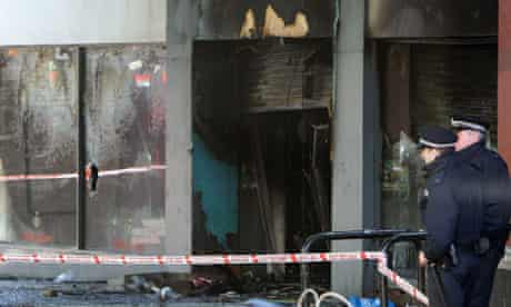 Police officers outside the burnt-out Footlocker store
