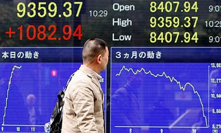 Man passes electronic board displaying Nikkei share average in Tokyo
