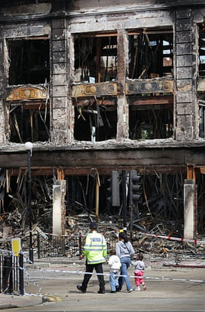 London Riots: A police officer escorts a family past the burnt out Carpetright shop