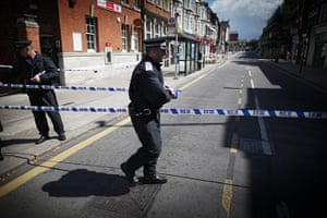 London Riots: A policeman puts tape across Church Street in Enfield